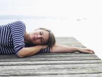 Germany, Munich, Mature woman relaxing on jetty beside lake