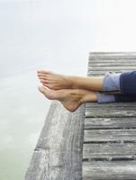 Germany, Munich, Mature woman relaxing on jetty near lake
