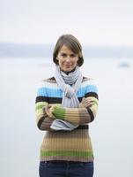 Germany, Munich, Mature woman near lake, smiling, portrait