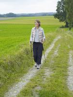Germany, Munich, Mature woman nordic walking, smiling 20025328740| 写真素材・ストックフォト・画像・イラスト素材|アマナイメージズ
