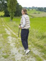 Germany, Munich, Mature woman nordic walking, smiling, portrait 20025328742| 写真素材・ストックフォト・画像・イラスト素材|アマナイメージズ