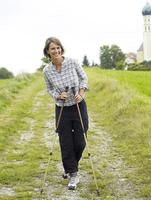 Germany, Munich, Mature woman nordic walking, smiling, portrait 20025328746| 写真素材・ストックフォト・画像・イラスト素材|アマナイメージズ
