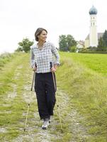Germany, Munich, Mature woman nordic walking, smiling 20025328747| 写真素材・ストックフォト・画像・イラスト素材|アマナイメージズ