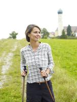 Germany, Munich, Mature woman nordic walking, smiling 20025328749| 写真素材・ストックフォト・画像・イラスト素材|アマナイメージズ