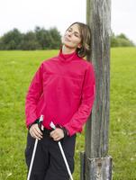 Germany, Munich, Mature woman leaning on tree with nordic walking pole, smiling 20025328750| 写真素材・ストックフォト・画像・イラスト素材|アマナイメージズ