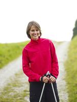 Germany, Munich, Mature woman with nordic walking pole, smiling, portrait 20025328752| 写真素材・ストックフォト・画像・イラスト素材|アマナイメージズ