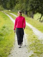 Germany, Munich, Mature woman nordic walking, smiling 20025328755| 写真素材・ストックフォト・画像・イラスト素材|アマナイメージズ