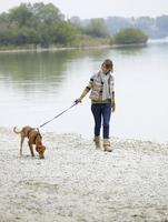 Germany, Munich, Mature woman near lake with dog, smiling 20025328763| 写真素材・ストックフォト・画像・イラスト素材|アマナイメージズ
