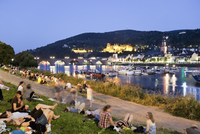 Germany, Heidelberg, People on river bank with castle in background 20025328774| 写真素材・ストックフォト・画像・イラスト素材|アマナイメージズ