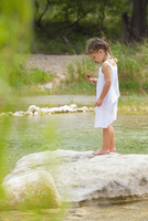 USA, Texas, Girl holding lollipop and standing on rock at Frio River 20025328831| 写真素材・ストックフォト・画像・イラスト素材|アマナイメージズ