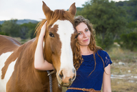 USA, Texas, Young woman standing with Quarterhorse, smiling, portrait