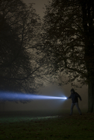 Germany, Munich, Man lighting spooky tree with torch in foggy night