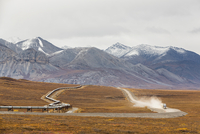 USA, Alaska, View of Trans Alaska Pipeline System along Dalton Highway with truck in autumn and Brooks Range