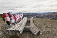 Canada, Dawson City, Wooden bench with carving and crochet cover at top of Midnight Dome