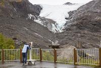 USA, Alaska, Tourist looking through binocular at Worthington Glacier 20025328989| 写真素材・ストックフォト・画像・イラスト素材|アマナイメージズ