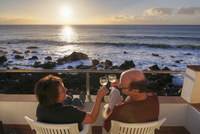 Spain, La Gomera, Mature couple sitting on terrace with white wine 20025329164| 写真素材・ストックフォト・画像・イラスト素材|アマナイメージズ