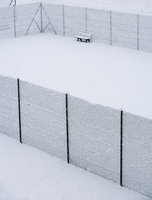 Austria, Styria, Bench and fence covered with snow at tennis court