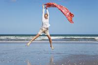 New Zealand, Mature woman jumping at Ninety Mile Beach 20025329354| 写真素材・ストックフォト・画像・イラスト素材|アマナイメージズ