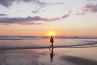 New Zealand, View of mature woman walking along beach 20025329357| 写真素材・ストックフォト・画像・イラスト素材|アマナイメージズ