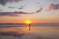 New Zealand, View of mature woman walking along beach 20025329358| 写真素材・ストックフォト・画像・イラスト素材|アマナイメージズ