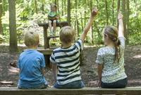 Germany, Bavaria, Munich, Friends playing school in woods 20025329402| 写真素材・ストックフォト・画像・イラスト素材|アマナイメージズ