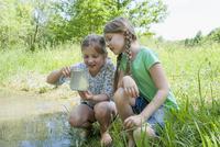 Germany, Bavaria, Munich, Girls playing at lake side