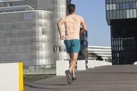 Germany, North Rhine Westphalia, Duesseldorf, Mid adult man jogging over bridge 20025329431| 写真素材・ストックフォト・画像・イラスト素材|アマナイメージズ