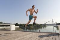 Germany, North Rhine Westphalia, Duesseldorf, Mid adult man jumping