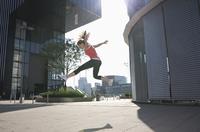 Germany, North Rhine Westphalia, Duesseldorf, Young woman jumping 20025329442| 写真素材・ストックフォト・画像・イラスト素材|アマナイメージズ