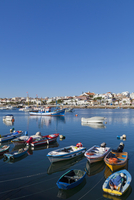 Portugal, Lagos, View of fishing boats at harbour and city in background