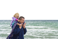 Denmark, Father carrying daughter on shoulder at beach, smiling