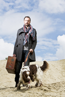 Germany, Bavaria, Man with dog standing in sand