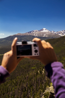 USA, Colorado, Rocky Mountain National Park, Woman taking a picture of Longs Peak and Mount Meeker 20025330212| 写真素材・ストックフォト・画像・イラスト素材|アマナイメージズ
