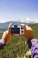 USA, Colorado, Rocky Mountain National Park, Woman taking a picture of Longs Peak and Mount Meeker