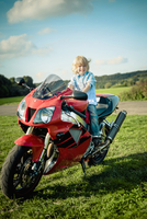Germany, Saxony, little boy sitting on red motorcycle