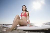 Germany, St Peter-Ording, young woman with stand up paddling surfboard at beach 20025330238| 写真素材・ストックフォト・画像・イラスト素材|アマナイメージズ