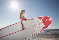 Germany, St Peter-Ording, young woman with stand up paddling surfboard at beach 20025330242  写真素材・ストックフォト・画像・イラスト素材 アマナイメージズ