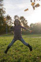 Little girl throwing autumn leaves while jumping