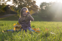 Little girl with autumn leaves sitting on a meadow 20025330262| 写真素材・ストックフォト・画像・イラスト素材|アマナイメージズ
