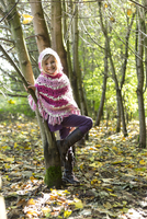 Germany, Vilsbiburg, Girl in forest, wearing poncho