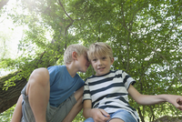 Germany, Bavaria, boy whispering into the ear of his friend 20025330404| 写真素材・ストックフォト・画像・イラスト素材|アマナイメージズ
