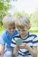 Germany, Bavaria, two boys looking at a compass 20025330408| 写真素材・ストックフォト・画像・イラスト素材|アマナイメージズ