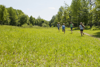 Germany, Bavaria, four children runnig on a meadow