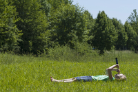 Germany, Bavaria, girl lying in gras and looking in the sky with binoculars 20025330411| 写真素材・ストックフォト・画像・イラスト素材|アマナイメージズ