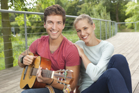 Germany, North Rhin Westphalia, Duesseldorf,  Portrait of young man and young woman with guitar, smiling 20025330431| 写真素材・ストックフォト・画像・イラスト素材|アマナイメージズ