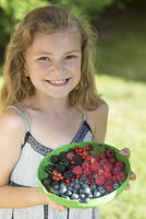 Germany, Bavaria, Portrait of girl holding beeries bowl, smiling