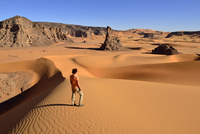 Algeria, Tassili n' Ajjer, Tadrart, Sahara, Tassili n' Ajjer National Park, woman in front of sanddunes and rocks of Moul Naga 20025330734| 写真素材・ストックフォト・画像・イラスト素材|アマナイメージズ