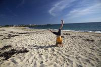 France, Bretagne, Finistere, Trevignon, Girl doing cartwheel on beach 20025330826| 写真素材・ストックフォト・画像・イラスト素材|アマナイメージズ