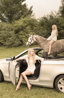 Young woman sitting in cabriolet while teenage girl riding on a horse in the background 20025330843| 写真素材・ストックフォト・画像・イラスト素材|アマナイメージズ