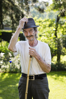 Portrait of senior man with hat and moustache standing in the garden